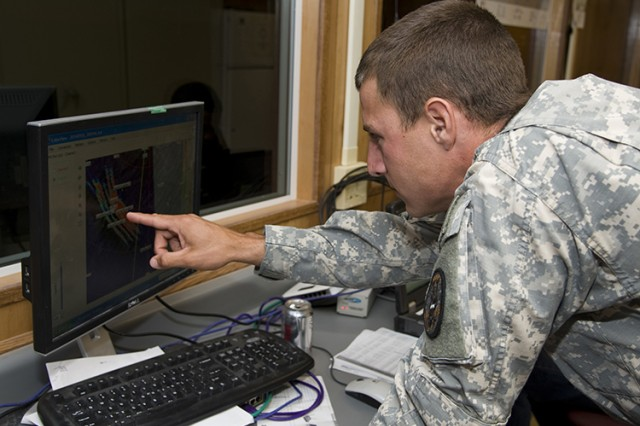 A U.S. Soldier in the Army Chemical Corps points to a cloud of simulated agent onscreen, during the 2014 S/K Challenge. Observing how the disseminated simulant moves and spreads is enlightening, especially to a Soldier trained to respond to chemical attacks or incidents. (Photo by Al Vogel / Dugway Public Affairs)