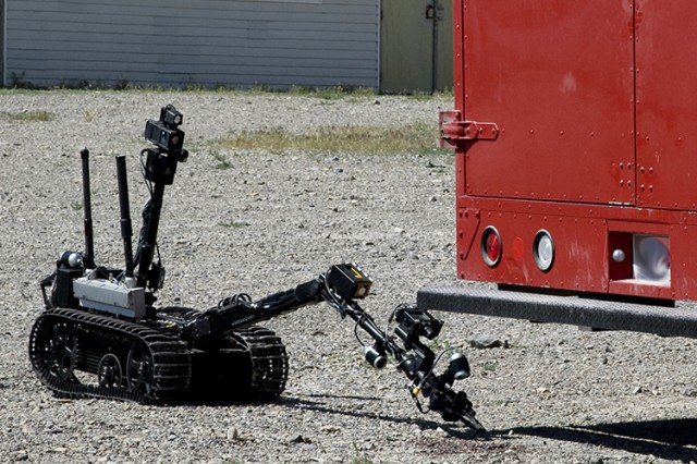"During each S/K Challenge there is a V.I.P. day, where participants display and explain their technology, and Dugway demonstrates some capabilities. Here, a remotely controlled robot takes surface samples from around a vehicle ""contaminated"" with a simulated chemical agent. Later, the vehicle was decontaminated with hoses using a water solution. (Photo by Al Vogel / Dugway Public Affairs)"