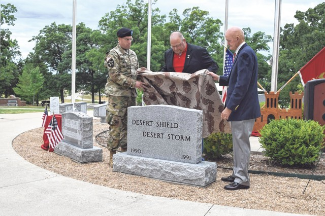 Brig. Gen. James Raymer, U.S. Army Engineer School commandant, left, Master Sgt. (retired) Bruce Harmon, center, and Lt. Gen. (retired) Daniel Schroeder unveil a stone commemorating Desert Shield and Desert Storm during a ceremony Friday in Soldier Memorial Grove.