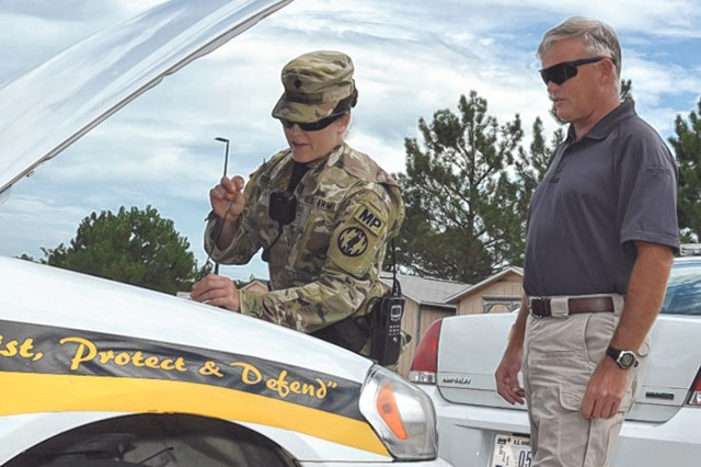 Don Rose, Directorate of Emergency Services deputy director, observes Spc. Brittany Cullip, 252nd Military Police Detachment, inspecting her patrol vehicle. Rose's instincts led him to help a woman rescue an infant from a locked vehicle.