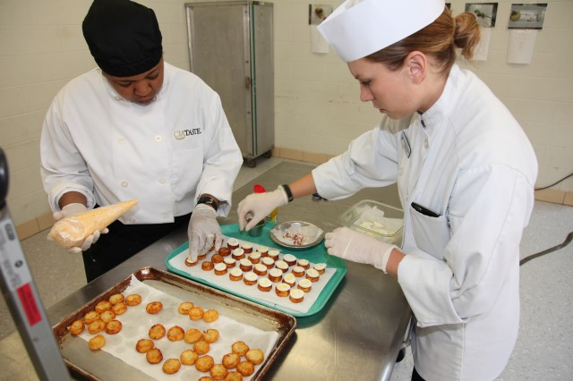 "Air Force Tech Sgt. Rosalie Freeman (right), the enlisted aide to the Defense Contract Management Agency director here and Air Force Staff Sgt. Brittany Stephens from Scott Air Force Base, Illinois, stack ""deviled"" quail eggs on a parmesan potato tot for an appetizer June 15 during the Advanced Culinary Training Course luncheon.  The Air Force NCOs are ""newbies"" to their military culinary career:  Stephens has been working in the food service industry just under a year and Freeman, about two months.  Freeman chose to attend the Advanced Culinary Course because she enjoys serving others.  ""As an EA, my primary mission is the well-being of my general officer,"" she said.  Stephens sees her job as a form of art and enjoys getting to work closely with her sister services."