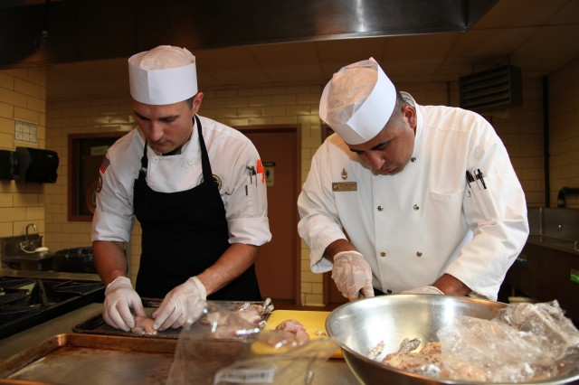 "Navy Senior Chief Tommy Chavira (right) is an enlisted aide stationed in Jacksonville, Fla.  Although he and Sgt. Adam Hermann -- who cooks at the Pentagon -- were not able to secure their first choice of fowl for the meal, they make do with fabricating an airline chicken breast.  The poultry was seared and served with a roasted garlic cream sauce.  The ""airline"" in the chicken breast has nothing to do with the environment in which it is prepared or served as the name may suggest, even though chicken served at 30,000 feet is often cut this way.  The ""airline"" refers to how the chicken is cut, a method that essentially results in a boneless chicken breast —except for an attached drumette.  Chavira was working in the food industry before he joined the military in 1999 when he felt a desire to serve in the military.  ""I was doing this already, so why not do it in the service,"" Chavira said.  Hermann was also a chef on the outside before signing up to serve.  ""This is what I love, so whether it's in the Army or in the civilian sector, I will be in food service,"" Hermann said."