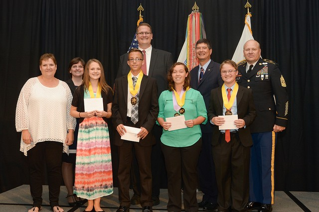 """Silver Bullet"" team members, from left, team advisor Laura Wilbanks, Elizabeth Casarez, Kaden Moses, Blade Henry and Kaylah Deavours receive national honors from (rear, from left) Mary Miller, DASD(R&E), Michael Holthe, DASA(R&T) and RDECOM's EDCG Jyuji Hewitt and CSM James Snyder.  The team looked for cost-effective ways to heal wounds in a world with antibiotic-resistant bacteria."