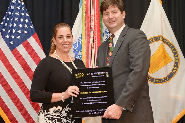 Jennifer Roberts, a sixth and eighth grade science educator at Coral Springs Middle School in Coral Springs, Florida, was named eCYBERMISSION Team Advisor of the Year.  Roberts encouraged all the science teachers at her school to adopt eCYBERMISSION into their curriculum, allowing all students the opportunity to participate. Since 2002, Roberts has implemented the eCYBERMISSION program into her curriculum and has served as a team advisor to six winning teams. Presenting Roberts her award is Jeffrey Singleton, director for Basic Research, Office of the Secretary of the Army (Acquisition, Logistics & Technology).
