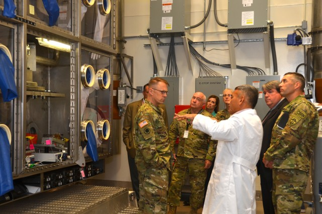 Dr. Wing Tsang (in the white lab coat) describes the Whole System Live Agent Test chamber at Dugway Proving Ground as unique. It's the first in the Department of Defense. Tsang and others believe it is the laboratory first in the world designed to test detectors and identifiers whole system not just the individual components that would warn of the presence of biological agent aerosols and identify the agent. Touring the facility was Maj. Gen. Brian C. Lein, commanding general, U.S. Army Medical Research and Material Command at Fort Detrick, Md., Dr. August W. Fountain acting director of research and technology, Edgewood Chemical and Biological Center and Col. Neal C. Wollen, director of biosecurity, U.S. Army Medical Research Institute of Infectious Diseases. (Photo by Bonnie A. Robinson, Dugway Public Affairs)