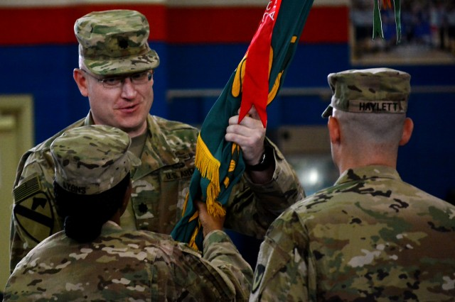 Lt. Col. Russell Foster, outgoing commander, 401st Army Field Support Battalion-Kuwait, receives the unit colors from Sgt. Maj. Velma Lyons, sergeant major, 401st AFSBn-Kuwait during a change of command ceremony for the 401st AFSBn-Kuwait at Camp Arifjan, Kuwait, July 1. (U.S. Army Photo by Justin Graff, 401st AFSB Public Affairs)