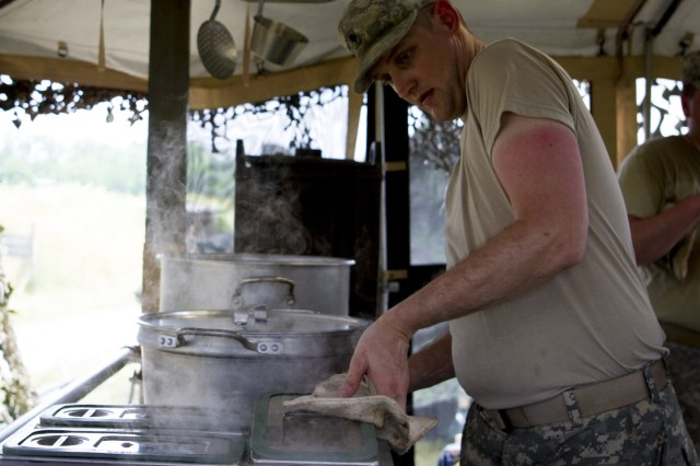 Spc. Sean Dubois, a U.S. Army Reserve culinary specialist from Euclid, Ohio, with the 391st Military Police Battalion, prepares to serve lunch during the Philip A. Connelly Competition at Camp Atterbury, Indiana, June 23. The 391st is representing the 200th MP Command in the competition, part of a training program designed to improve professionalism and recognize excellence, which augments the quality of food and food service within the Army. The top four food service teams will continue to the U.S. Army Reserve level competition. (U.S. Army photo by Sgt. Audrey Hayes)
