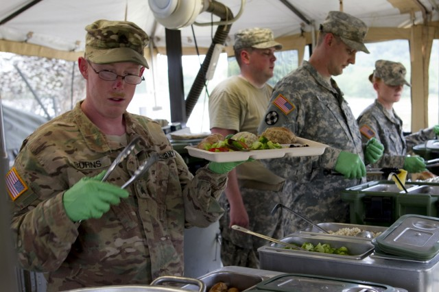 Sgt. Justin Burns, a U.S. Army Reserve culinary specialist from Columbus, Ohio, with the 391st Military Police Battalion, serves lunch to Soldiers during the Philip A. Connelly Competition at Camp Atterbury, Indiana, June 23. The 391st is representing the 200th MP Command in the competition, part of a training program designed to improve professionalism and recognize excellence, which augments the quality of food and food service within the Army. The top four food service teams will continue to the U.S. Army Reserve level competition. (U.S. Army photo by Sgt. Audrey Hayes)