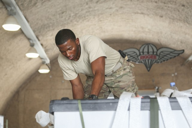 "Sgt. Maurice Banks, parachute rigger from Columbus, Georgia with the 824th Quartermaster Company. (Detachment 1) ""Riggers,"" 17th Sustainment Brigade, 1st Sustainment Command (Theater), ties a knot on top of a container delivery system here June 16, 2016. Banks acknowledges that rigging is physically demanding work, especially on the hands, but he knows his efforts are vital in supporting the deployed warfighter."