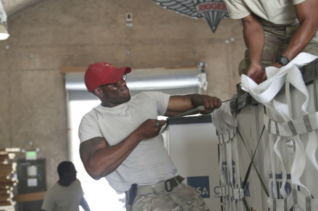 "Sgt. Ryan Fraser (left), operating noncommissioned officer from Atlanta, Georgia with the 824th Quartermaster Company. (Detachment 1) ""Riggers,"" 17th Sustainment Brigade, 1st Sustainment Command (Theater), strains to tighten a knot on a container delivery system with assistance from Sgt. Maurice Banks here June 16, 2016. Banks, from Columbus, Georgia, is a parachute rigger in the same unit. Preparing a CDS for airdrop requires more than 20 knots and three inspections."