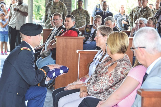 2nd Lt. Charles Hachat, 50th Multi Role Bridge Company, presents Gloria McBeth, Assistance Association of the Missouri Veterans Cemetery — Fort Leonard Wood board member, with the flag representing retired Sgt. 1st Class James Matisheck's service. The Fort Leonard Wood community became Matisheck's extended Family during his funeral June 29.