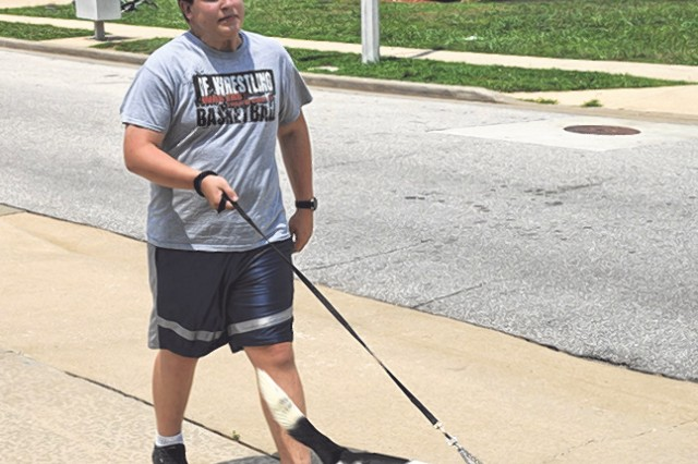 Daniel Rodrigues walks the Family pet, Kiko, in the Eagle Point neighborhood Monday. Fort Leonard Wood Policy 40-4 states a maximum of two dogs or cats are allowed to reside in/at each authorized housing unit.