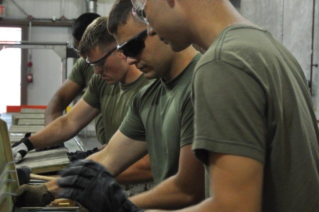 Marine Corps Reservists with the Combat Logistics Battalion 453 out of Topeka, Kansas, inspect ammunition at Crane Army Ammunition Activity's Surveillance Facility.  During their two week annual training Marines had exposure to all aspects of ammunition handling. This included inventory, surveillance, storage, shipping and receiving, blocking and bracing, and demolition.