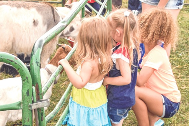 A Family spends some time with the animals at the Independence Day Celebration petting zoo. Photo by Caitlyn Marler/FMWR marketing