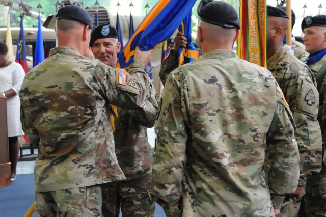 Col. Michael E. Demirjian, ATSCOM and 164th TAOG commander, assumes command from Col. Douglas Van Weelden III as he accepts the unit colors from Lt. Gen. Patrick J. Donahue II, U.S. Army Forces Command deputy commanding general, during a ceremony at the U.S. Army Aviation Museum June 28.
