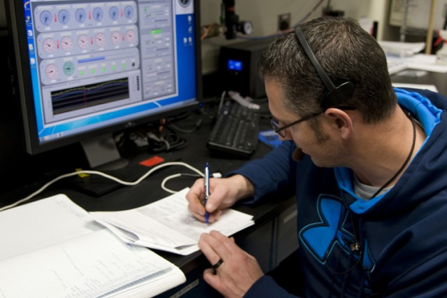 Nathan Otasua, test control officer for the Common Analytical Laboratory System (CALS) test at Dugway Proving Ground, collects data and makes notes. Otasua is also a glovebox chamber operator. (Photo by Al Vogel / Dugway Public Affairs)