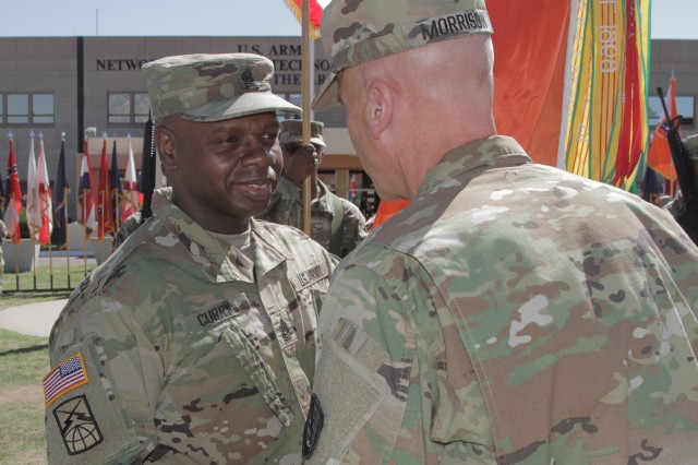 Command Sgt. Maj. Darris Curry receives the NETCOM colors from Maj. Gen. John Morrison Jr., during the change of responsibility ceremony July 12, in front of Greely Hall, Fort Huachuca, Arizona.