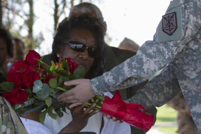 A Soldier from the 200th Military Police Command presents Robin Churn, Maj. Gen. Phillip M. Churn's wife, a bouquet of red roses in appreciation of her attributions to the unit during the 200th MP Cmd's relinquishment of command ceremony at the McGlachlin Parade Field, at Fort Meade, Md., July 10, 2016.  Lieutenant General Charles D. Luckey, chief of the Army Reserve and commanding general of the United States Army Reserve Command, was the reviewing official for the ceremony, in which Maj. Gen. Phillip M. Churn relinquished command to Brig. Gen. Marion Garcia. (U.S. Army photo by Spc. Stephanie Ramirez)