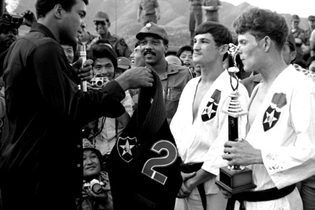 During his 1976 visit to Camp Casey in Dongducheon, world heavyweight boxing champion Muhammad Ali is presented a 2nd Infantry Division sweater in recognition of his visit, during which he gave a 20-minute talk to more than 2,500 division troops, boxed a few exhibition rounds with Soldiers, and watched a martial arts demonstration by Spec. 4 James Sylvester and Sgt. Fletcher Woods.