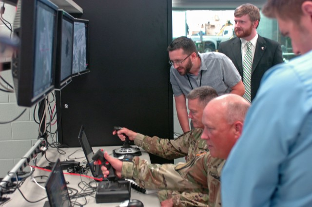 Gen. Daniel Allyn, Vice Chief of Staff of the Army, and Maj. Gen. James Richardson, Acquisition Reform Lead, take the controls of the TARDEC Virtual Experiments Capability during a visit to the U.S. Army Tank Automotive Research, Development and Engineering Center, Warren, Mich., July 7, 2016. Gen. Allyn came to TARDEC, the leader for the Army's ground vehicle integration, to become familiar with its capabilities to include organic prototyping and autonomous operations. (Photo by Kimberly Bratic, TARDEC Public Affairs/Released)
