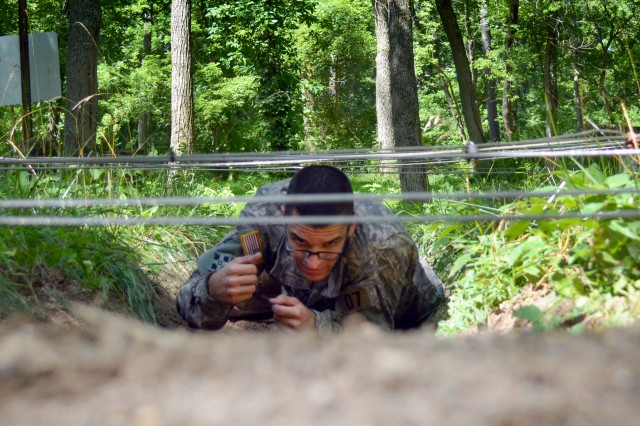 Sgt. Henrique Magalhaes, chaplain's assistant, U.S. Army Sustainment Command navigates under simulated trip wire at a six-station obstacle course, Camp Atterbury, July 7.
