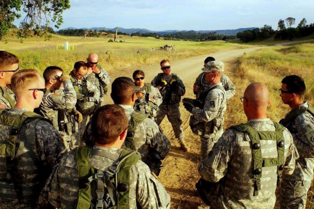 Staff Sgt. Travis Barr, an observer coach/trainer assigned to the 3rd  Battalion, 340th  Regiment (Brigade Engineer Battalion), 181st Infantry Brigade, talks to Soldiers from the 1st  Platoon, 208th  Transportation Company out of Marana, Arizona about troop leading procedures (TLPs) prior to a convoy mission at Fort Hunter-Liggett, California, May 11.