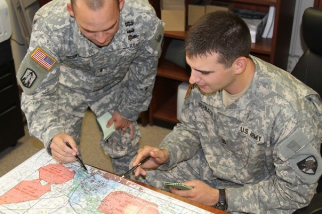 1st Lt. Chris Schwen, executive officer for A Company, 168th Brigade Support Battalion, and then-Cadet Robert Schrack discuss possible routes for a convoy operation. The Army's Cadet Troop Leadership Training program gives West Point and ROTC cadets nearly a month to work side-by-side with lieutenants in active Army units worldwide.
