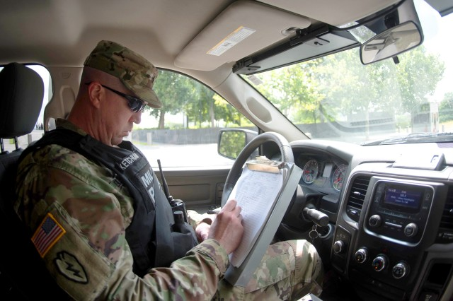 U.S. Army Sgt. Timothy Ketchum, a military police officer with the 3d U.S. Infantry Regiment's (The Old Guard) 289th Military Police Company, fills out paperwork while performing roving patrols at Joint Base Myer-Henderson Hall June 26. Ketchum is one of dozens of uniformed MPs who patrol, respond and enforce laws and regulations at all three portions of JBM-HH and inside Arlington National Cemetery.