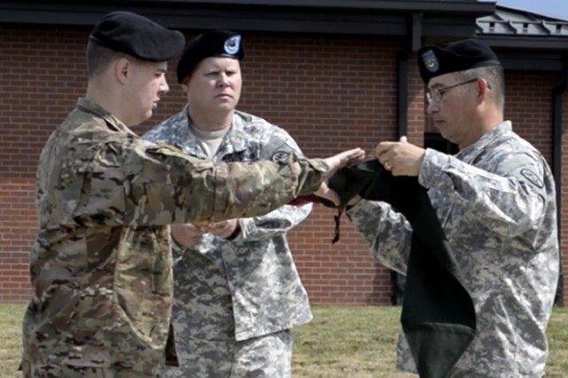 Capt. Adam Hamilton and 1st Sgt. Bradford Raven, Warrior Transition Unit commander and first sergeant, respectively, case the WTU guidon during the unit's inactivation ceremony June 30.