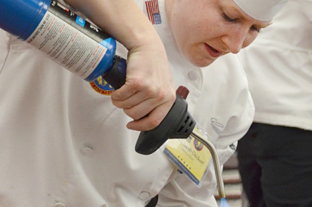 Sgt. Sarah Deckert, Enlisted Aide to the Surgeon General of the Army and Commanding General, U.S. Army Medical Command, melts chocolate cake icing with a torch during a military culinary arts competition at Fort Lee, Virginia, in March 2014. Enlisted Aide selectees participate in exceptional training opportunities and serve as valued team members of general officers across the Army and around the world.