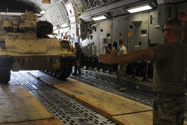 A Soldier assigned to Company A, 1st Battalion, 9th Cavalry Regiment, 2nd Armored Brigade Combat Team, 1st Cavalry Division, guides the driver of a Bradley Fighting Vehicle as it is loaded onto a C-17 Globemaster III during a training event July 15, at Robert Gray Army Airfield on Fort Hood, Texas. (U.S. Army photo by Staff Sgt. Johnathan Hoover, 2nd BCT PAO, 1st Cav. Div.)
