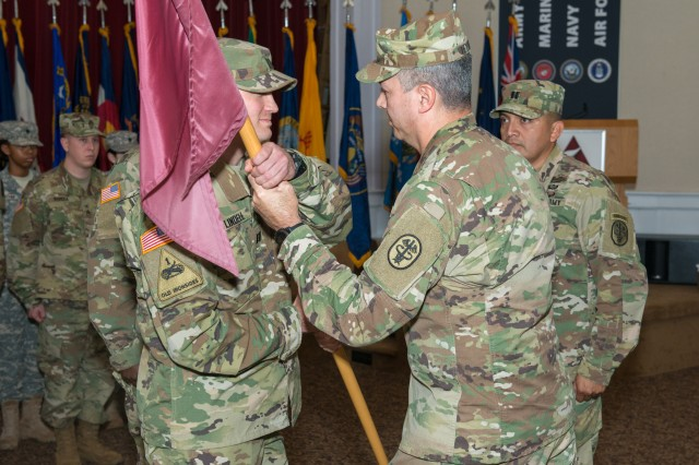 Capt. Ryan Lindell, incoming commander of APHC (P)'s Headquarters and Headquarters Company, receives the unit colors from Col. John V. Teyhen, then-deputy director of APHC (P).