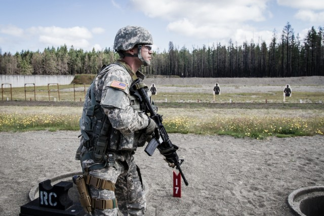 A U.S. Army Soldier, assigned to 16th Combat Aviation Brigade, 7th Infantry Division, prepares to fire an M4 carbine during a reflexive-fire range at Joint Base Lewis-McChord, Wash., July 18, 2016. The range allowed Soldiers to use both the M4 carbine and M9 pistol to enhance weapon transition skills and marksmanship.