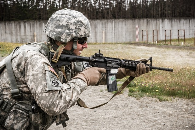 A U.S. Army UH-60 Black Hawk helicopter pilot, assigned to 16th Combat Aviation Brigade, 7th Infantry Division, prepares to fire an M4 carbine during a reflexive-fire range at Joint Base Lewis-McChord, Wash., July 18, 2016. The range allowed Soldiers to use both the M4 carbine and M9 pistol to enhance weapon transition skills and marksmanship.