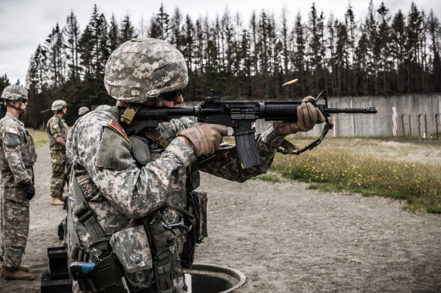 A U.S. Army Soldier, assigned to 16th Combat Aviation Brigade, 7th Infantry Division, fires an M4 carbine during a reflexive-fire range at Joint Base Lewis-McChord, Wash., July 18, 2016. The range allowed Soldiers to use both the M4 carbine and M9 pistol to enhance weapon transition skills and marksmanship.