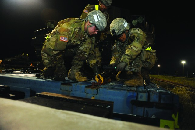 Soldiers from 2nd Battalion 8th Cavalry loosen the chains on their Bradley Fighting Vehicle to prepare it for movement off the rail car at the Camp Humphreys rail head July 13.