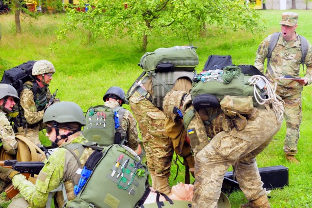 YAVORIV, Ukraine--Ukrainian Medics treat a simulated casualty while Staff Sgt. Derek Stutz, an instructor from the Army Medical Department, 232nd Medical Battalion provides encouragement and evaluation. The evaluation was part of a culminating training event at the International Peacekeeping and Security Center July 20. Soldiers from the United States Army Security Assistance Training Management Organization and instructors from the Army Medical Department in Fort Sam Houston, Texas were here to teach a three-month long combat medic instructor course.(Army photo by Capt. Scott Kuhn)