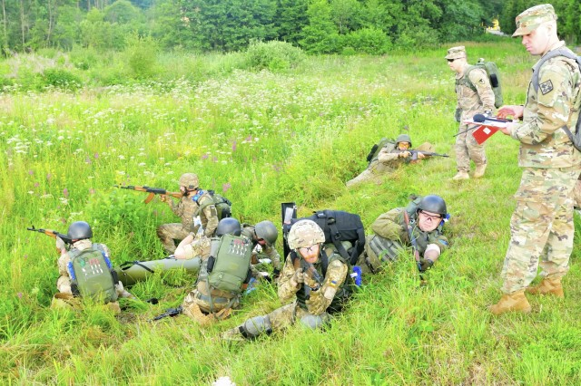 YAVORIV, Ukraine--Ukrainian Medics treat a simulated casualty while Staff Sgt. Derek Stutz (near), an instructor from the Army Medical Department, 232nd Medical Battalion and Sgt. First Class Shon Crowley (far)  an instructor with United States Army Security Assistance Training Management Organization evaluate them. The evaluation was part of a culminating training event at the International Peacekeeping and Security Center July 20. Soldiers from USASATMO and AMEDD in Fort Sam Houston, Texas were here to teach a three-month long combat medic instructor course. (Army photo by Capt. Scott Kuhn)