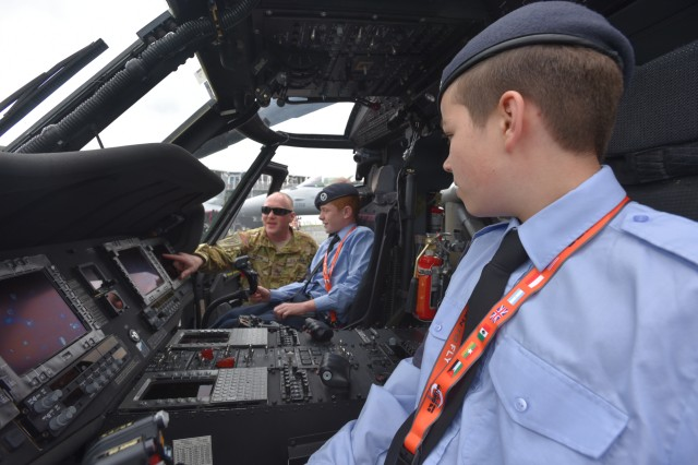 Sgt. Jason Hook, a 15T, Black Hawk Repairer from Charlie Company, 3rd Bn., 501st Avn. Regt., 1AD CAB, explains the UH-60M Black Hawk digitized cockpit to children from the British Air Scouts, 15 July, 2016, during the Farnborough Air and Trade show which took place, 11-17 July, at TAG Farnborough Airport.   Static helicopter displays demonstrate USAREUR's ability to project rotary wing combat power around Europe in an expedient manner.