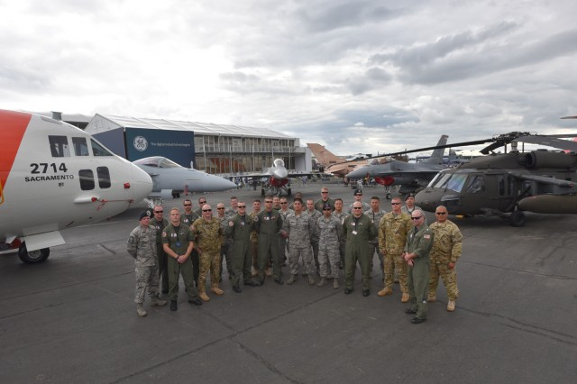 Soldiers, Sailors, and Airmen pose in front of their respective aircraft at the static display area, 15 July, 2016, during the Farnborough Air and Trade show which took place, 11-17 July, at TAG Farnborough Airport. Static helicopter displays demonstrate USAREUR's ability to project rotary wing combat power around Europe in an expedient manner.