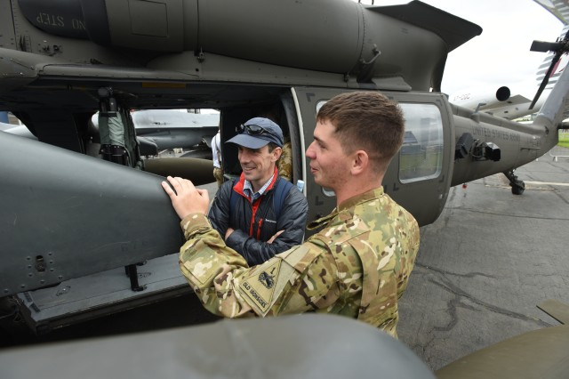 Pvt. Kris Paranteau, a 15T Black Hawk Repairer from Charlie Company, 3rd Bn., 501st Avn. Regt., 1AD CAB, explains the extended range fuel system on the UH-60M Black Hawk to an attendee, 15 July, 2016, during the Farnborough Air and Trade show which took place, 11-17 July, at TAG Farnborough Airport.   Static helicopter displays demonstrate USAREUR's ability to project rotary wing combat power around Europe in an expedient manner.