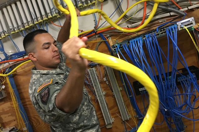 Cable Installer Sgt. Manuel Hernandez from Lubbock, Texas, pulls fiber optic cable through conduit at Operational Test Command. A Reserve Soldier from the 820th Signal Company (Tactical Installation Network) out of Seagoville, Texas, Hernandez is helping OTC save close to $97,000 installing communication cables in its headquarters on West Fort Hood, Texas.