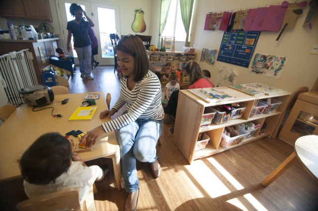 SEASIDE, California -- Adriana Rodriguez, a newly-certified Family Child Care provider, works with a child while attending a song-and-story hour in the home of Tiffiny Edwards, another FCC provider at Presidio of Monterey's Ord Military Community. Army Community Service's Family Child Care program matches the needs of military families seeking quality child care with family members seeking a portable career they can continue throughout their sponsor's time in service.