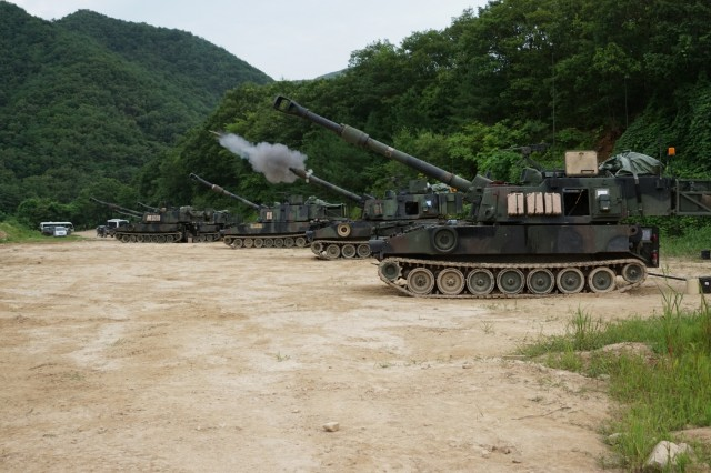 Soldiers from Battery B, 1st Battalion, 82nd Field Artillery Regiment, 1st Armored Brigade Combat Team, 1st Cavalry Division, fire a 155mm round from a battery of M109A6 Paladin self-propelled howitzers at Nightmare Range, near Topyong-ri, South Korea, from July 20.