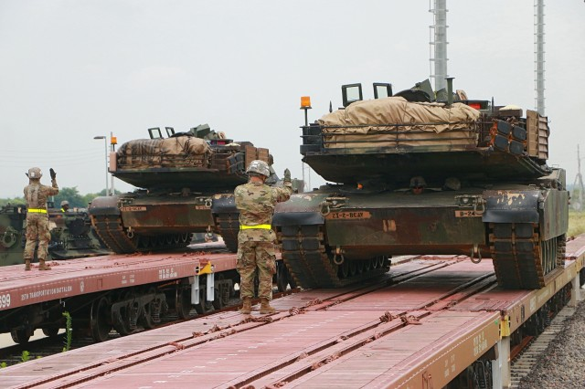 Soldiers from the 2nd Battalion, 5th Cavalry Regiment, 1st Armored Brigade Combat Team, 1st Cavalry Division, guide the unloading of M1A2 Abrams main battle tanks from Korean railcars July 13 on US Army Garrison Humphreys. The effort to move 2nd Bn, 8th Cav. Reg., 1st ABCT, from Camp Stanley to USAG Humphreys required the assistance of Soldiers from four battalions, including the 1st Squadron, 7th Cavalry Regiment, 1st ABCT; the 91st Engineer Bn., 1st ABCT; and the 115th Brigade Support Bn., 1st ABCT. (U.S. Army photo by Sgt. Christopher Dennis, 1st Armored Brigade Combat Team Public Affairs, 1st Cav. Div.)