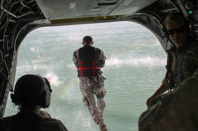 First Sgt. Brian Reeder of Headquarters and Headquarters Company, 308th Brigade Support Battalion, 17th Field Artillery Brigade jumps into American Lake from a CH-47 Chinook during a helocast July 22, 2016. The helocast was one of 17 events Reeder and his team faced during an 11-hour Mungadai that took them across Joint Base Lewis-McChord.