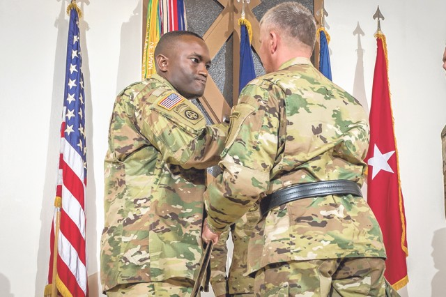 Chief Warrant Officer 2 Jesse Deberry accepts the saber from Brig. Gen. James Bonner, U.S. Army Chemical, Biological, Radiological and Nuclear School commandant, signifying his assuming responsibility as the 2nd Regimental Chief Warrant Officer.