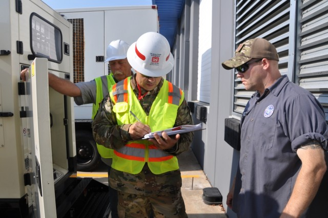 Participants of a temporary emergency power planning and response team check systems on a generator awaiting installation during a regional power mission exercise conducted July 20 at the Federal Emergency Management Agency Distribution Center in Atlanta, Georgia.