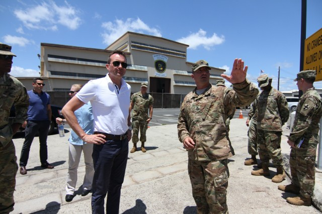 Sgt. First Class Tim Carman, 605th Transportation Co., greets Secretary of the Army Eric Fanning before leading him on a tour of Logistic Support Vessel-2, the CW3 Harold C. Clinger.
