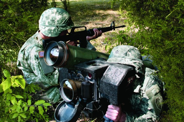 A Soldier readies the Javelin missile system for a target launch while another Soldier guards the area from enemy attack.